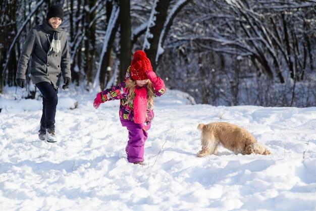 Vader en dochter en hond tijdens de winterwandeling