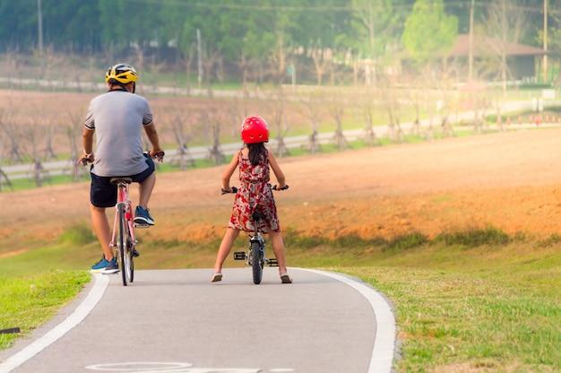 Vader en dochter fietsen samen op de betonweg in het park
