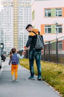 Vader en dochter gaan voor het eerst naar school. terug naar school na een pandemie.