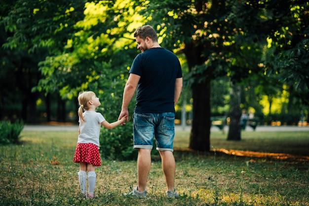 Vader en dochter hand in hand van achteren