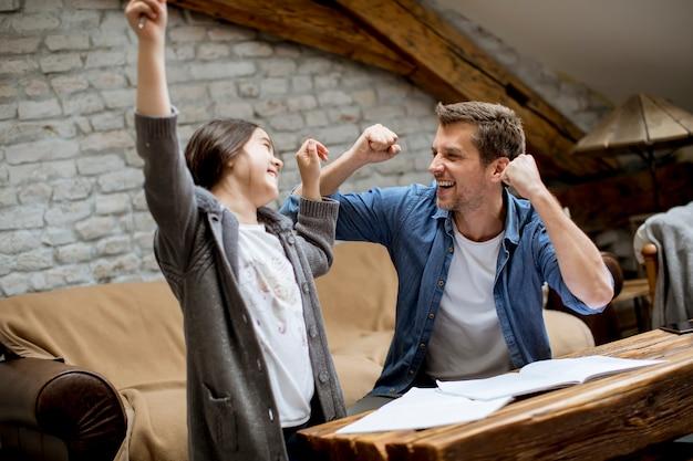 Vader en dochter hebben met succes huiswerk gemaakt in de kamer