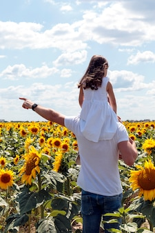 Vader en dochter hebben plezier in zonnebloemen veld. kid zit op papa's schouders op zomervakantie. kind meisje en man zijn familie.