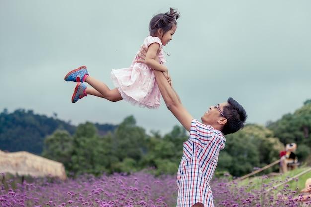 Vader en dochter hebben plezier om samen te spelen in de bloementuin