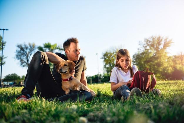 Vader en dochter het ontspannen bij park met hond
