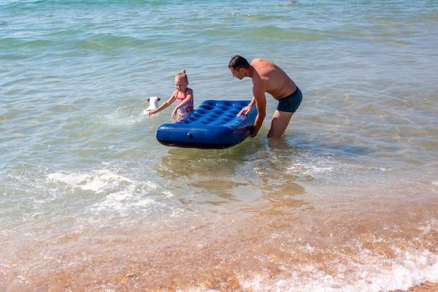 Vader en dochter in de zee rijden op een rubberen matras. zomer leuke vakanties.