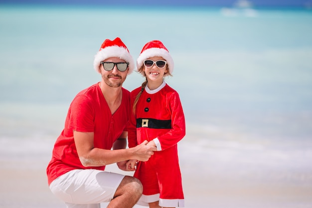 Vader en dochter in santa hat hebben plezier op tropisch strand