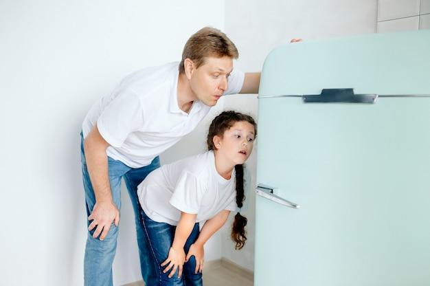Vader en dochter kijken emotioneel in de koelkast op zoek naar heerlijk eten om samen tijd door te brengen