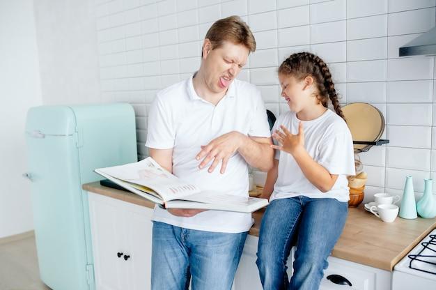 Vader en dochter kijken in de keuken naar een recept in een kookboek