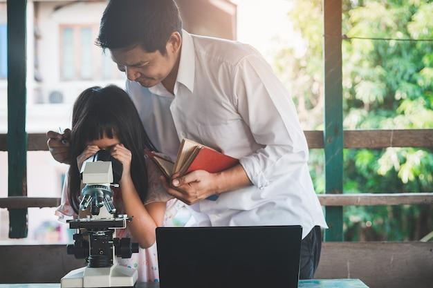 Vader en dochter leren van huis met laptop en kijken naar microscoop.coronavirus of covid-19 outbreak school sluitingen