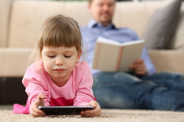 Vader en dochter liggen op de vloer met behulp van de mobiele telefoon