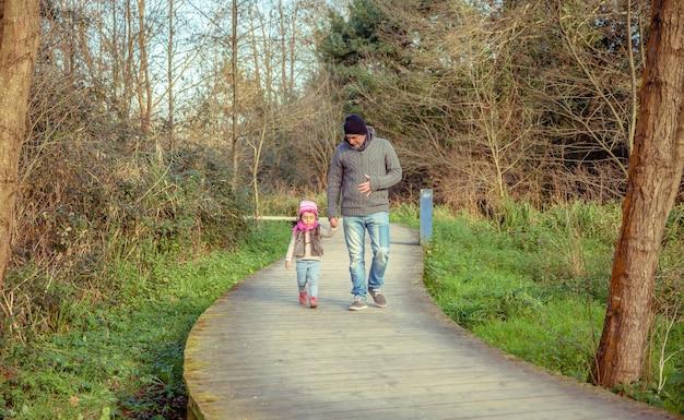 Vader en dochter lopen samen hand in hand over een houten pad naar het bos