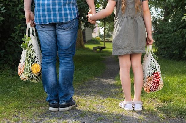 Vader en dochter met katoenen koordzakken, zakken boodschappen in de natuur