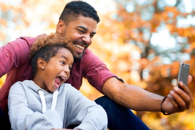 Vader en dochter nemen selfie met slimme telefoon terwijl ze grappige gezichten maken