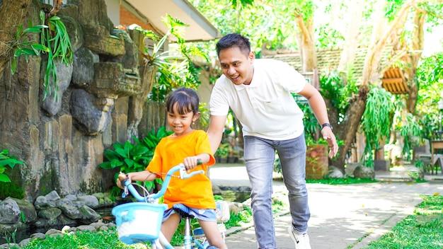 Vader en dochter oefenen fietsen in het park