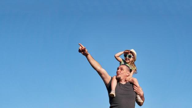 Vader en dochter op schouders verheugen zich gelukkig.