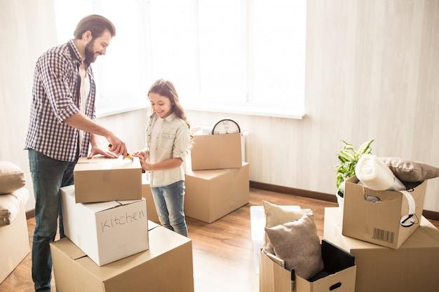 Vader en dochter pakken samen dozen uit. ze hebben veel werk te doen. ze zitten nu zonder hun moeder. deze mensen zien er gelukkig en tevreden uit.