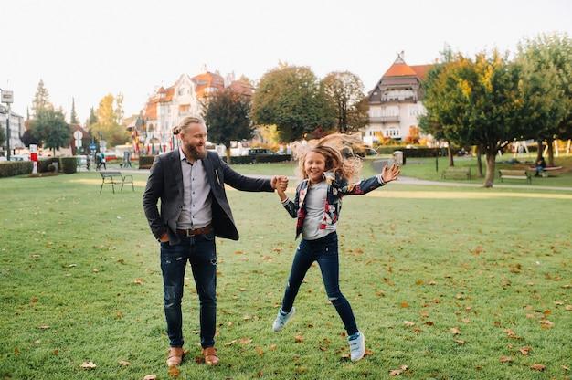Vader en dochter rennen op het gras in de oude stad van oostenrijk. een familie loopt door een kleine stad in oostenrijk.europa.felden am werten zien.