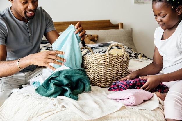 Vader en dochter samen vouwen kleren in de slaapkamer