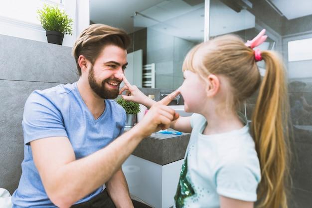 Vader en dochter smeren crème op neuzen