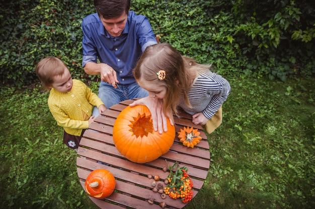 Vader en dochter snijdende pompoen voor halloween