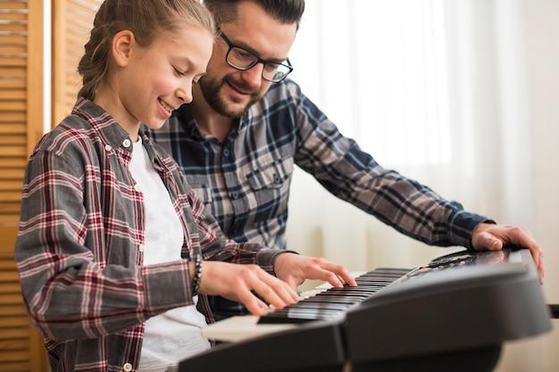 Vader en dochter spelen op de piano