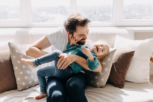 Vader en dochter spelen samen op de bank thuis