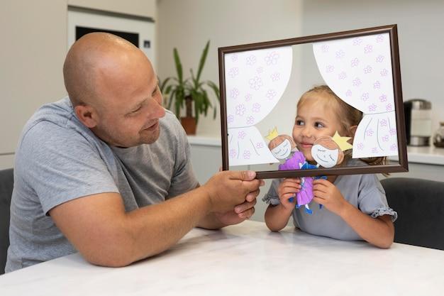 Vader en dochter spelen thuis met poppen