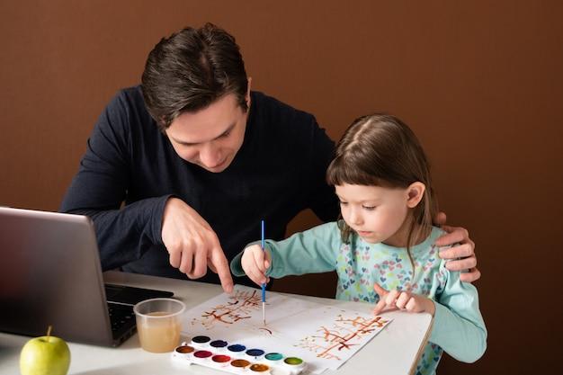 Vader en dochter tekenen thuis naast een laptop
