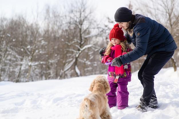 Vader en dochter trainen hun hond tijdens de winterwandeling