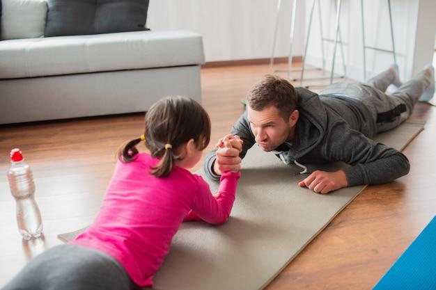 Vader en dochter trainen thuis. workout in het appartement. sport thuis. doe mee aan armworstelen en ga op een yogamat liggen