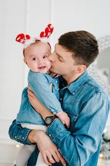 Vader en dochter. vrolijk kerstfeest. kerst versierd interieur. het concept van gezinsvakantie in de winter.