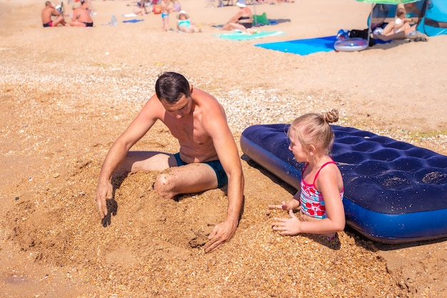 Vader en dochter zijn begraven in het zand aan de kust. zomer leuke vakanties.