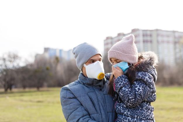 Vader en dochter zijn warm gekleed bij koud weer en dragen beschermende medische maskers op hun gezicht tijdens een griepepidemie of luchtvervuiling. een man en een kind in een stadsstraat