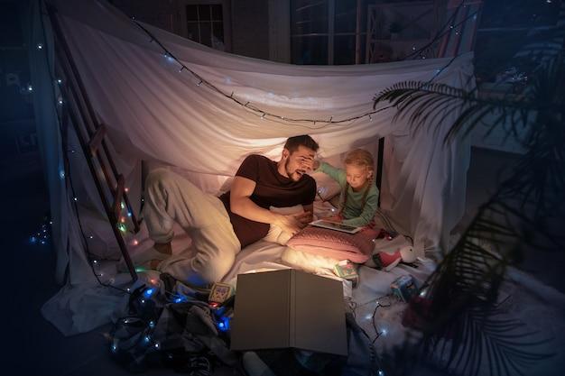 Vader en dochter zitten in een tipi, hebben plezier, spelen met de zaklamp in een donkere kamer met speelgoed en kussens. kijk gelukkig. thuiscomfort, familie, liefde, kerstvakantie, verteltijd.