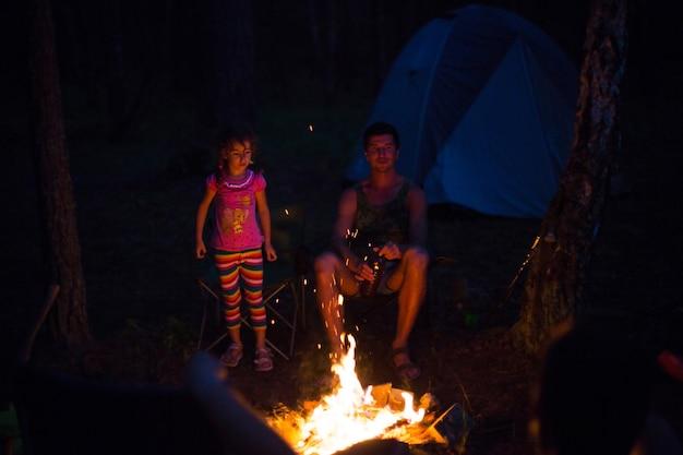 Vader en dochter zitten 's nachts bij het vuur in de open lucht in de zomer in de natuur. familie kampeeruitstapje, bijeenkomsten rond het kampvuur. vaderdag, barbecue. campinglantaarn en tent
