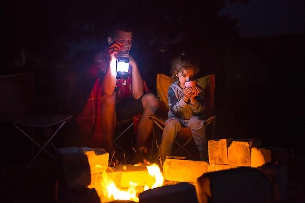 Vader en dochter zitten 's nachts bij het vuur in de open lucht in de zomer in de natuur.