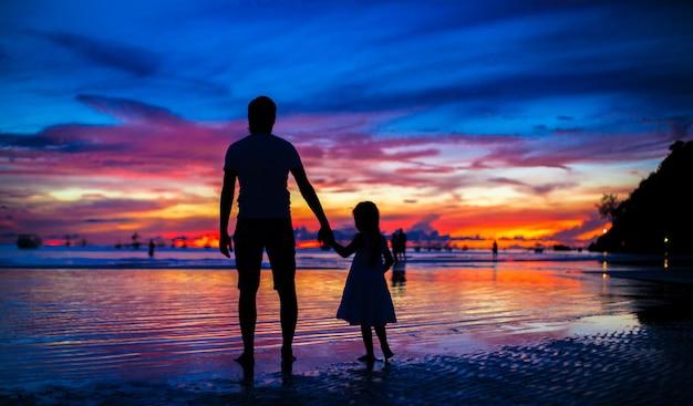 Vader en dochtersilhouetten in zonsondergang bij het strand op boracay