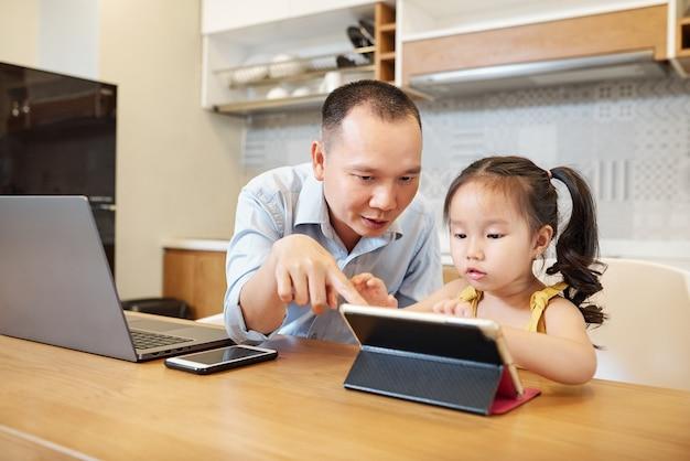 Vader en dochtertje speelspel samen op tabletcomputer zittend aan de keukentafel