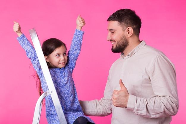 Vader en haar dochtertje met duimen omhoog over roze. volwassen man en babymeisje zijn blij.
