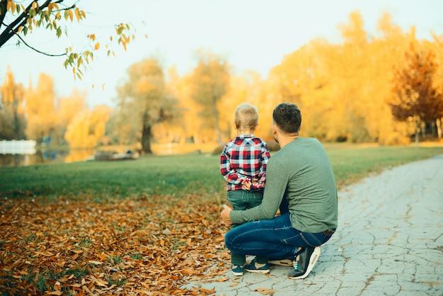 Vader en jongen buiten in het park op mooie herfst zonnige dag