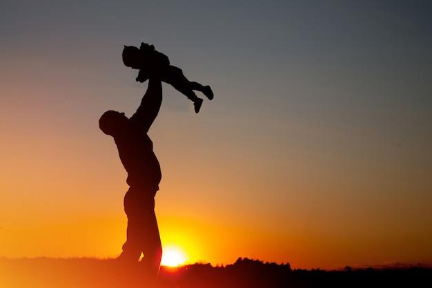 Vader en kind die de zonsondergangtijd spelen. concept van vriendelijke familie.