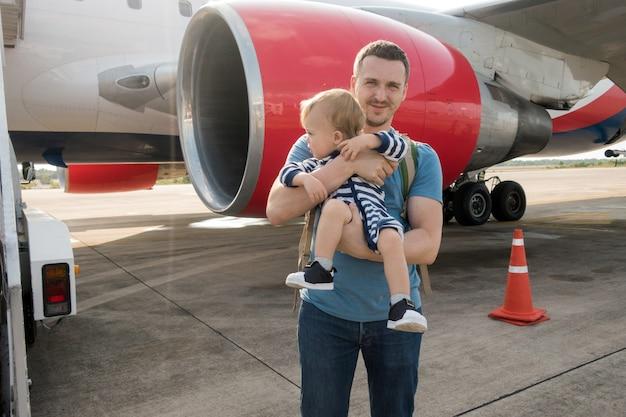 Vader en kind die op vliegtuig in luchthaven inschepen
