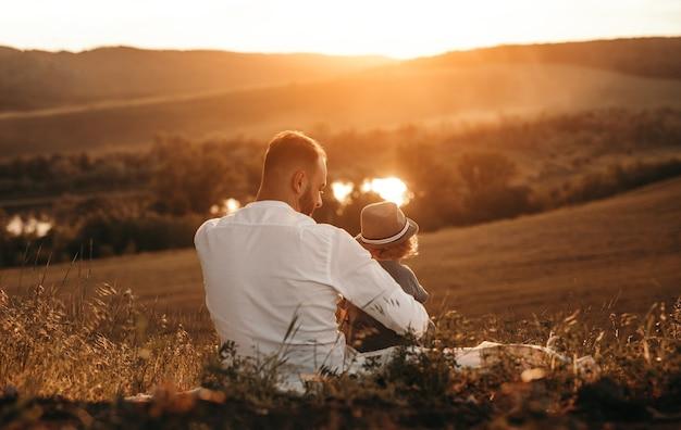 Vader en kind genieten van zonsondergang in de natuur
