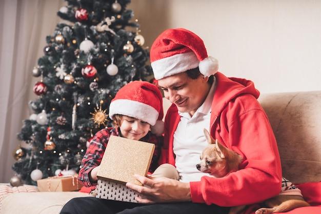 Vader en kind jongen open kerstcadeau thuis.