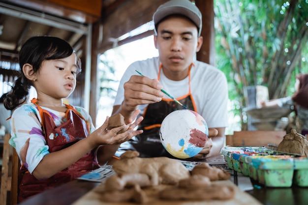 Vader en kind schilderen aardewerk goederen