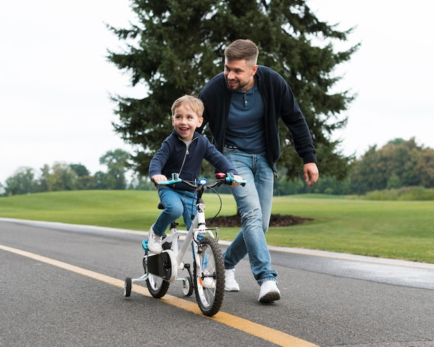 Vader en kind spelen in park lange weergave
