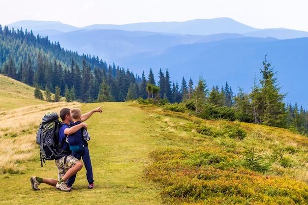 Vader en kind wandelen in schilderachtige bergen.