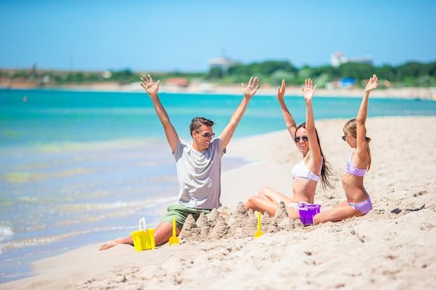 Vader en kinderen maken zandkasteel op tropisch strand. familie spelen met strand speelgoed