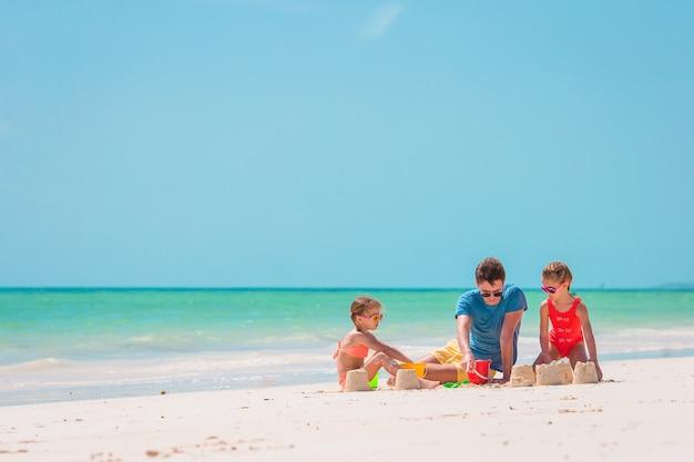 Vader en kinderen maken zandkasteel op tropisch strand. familie spelen met strandspeelgoed