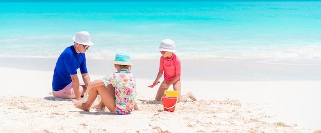 Vader en kleine dochters die zandkasteel maken bij tropisch strand
